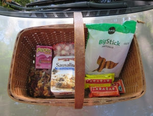 My Horse Show Road Trip Survival Kit assembled on the hood of the rental car: cookies for sweet (this flavor reserved for show weekends), pretzels for salt, yuppie gorp for nibbles, Lara bars & Glucerna for breakfast and other missed meals, Pepto & peppermints for a tum in various states of wiggliness. Food has been carefully tuned for (a) driving (b) to a horse show (c) by myself. If flying, I would take only the compact and TSA-compliant items. If no horse show, less of the nervous food. If Husband is going, he handles the food.